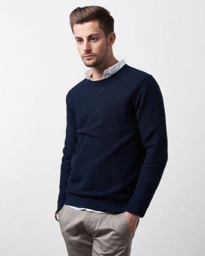 Till herr från Calvin Klein, en blå stickade tröja.
