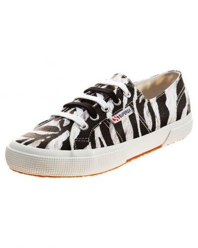 Till dam från Superga, en svart sneakers.