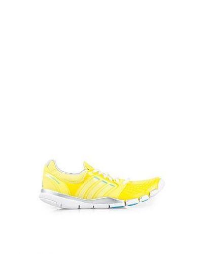 Till dam från adidas Performance, en gul träningssko.