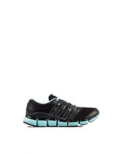 Till dam från adidas Performance, en svart träningssko.