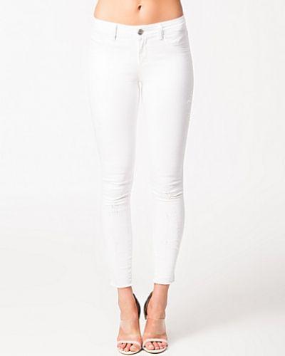 Till dam från Notion 1.3, en vit slim fit jeans.