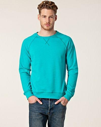 Till killar från Cheap Monday, en turkos sweatshirts.