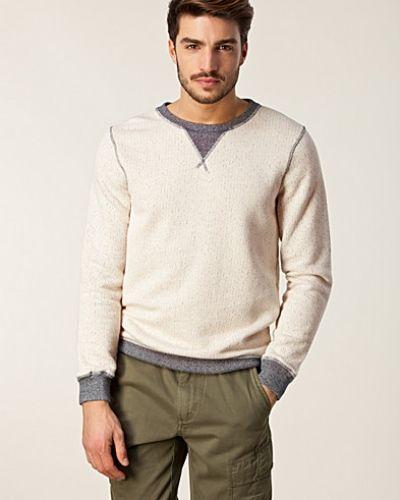 Till killar från Nudie Jeans, en beige sweatshirts.